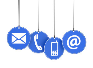 """Blue circles containing icons of an envelope, a landline phone, a cell phone, and an """"@"""" symbol."""