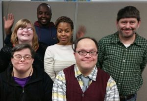 Six members of self advocacy network smiling and waving.