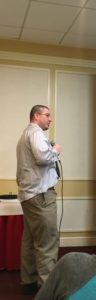Self advocacy coordinator James, a tall Caucasian man with short hair, standing and speaking into microphone.